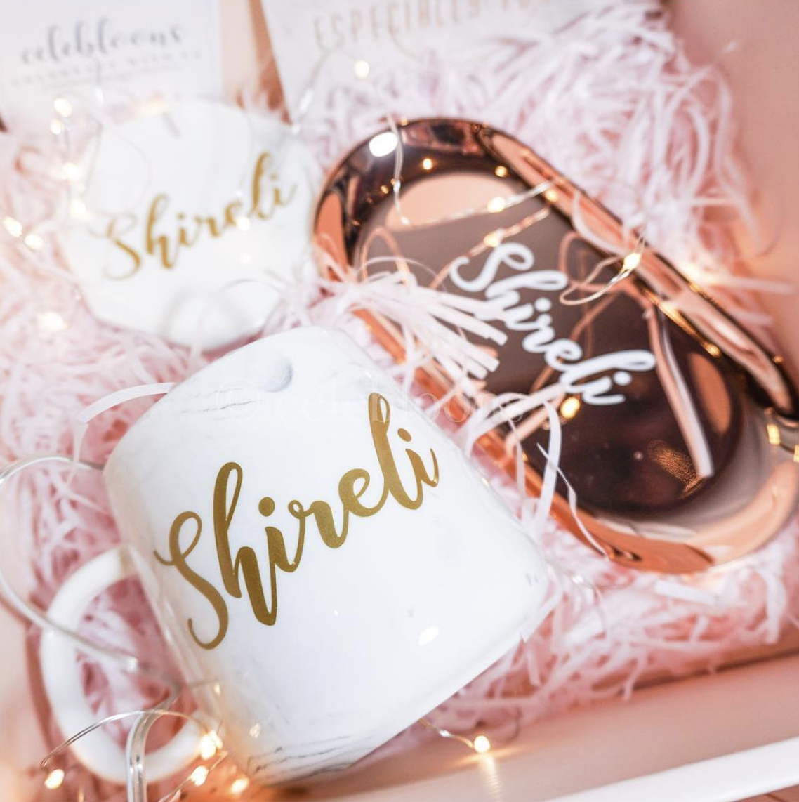 "A white mug, rose gold reflective trinket tray and hexagon coaster with the name ""Shireli"" on them"
