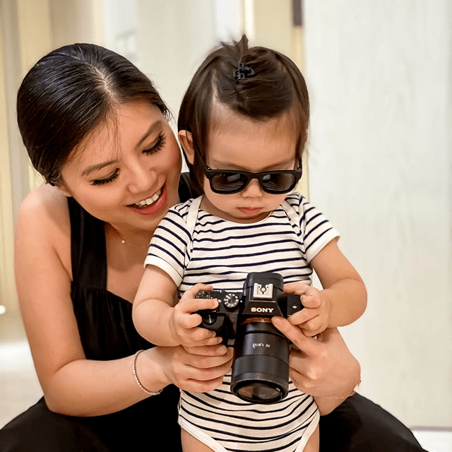 Woman in black dress holding her baby and a camera
