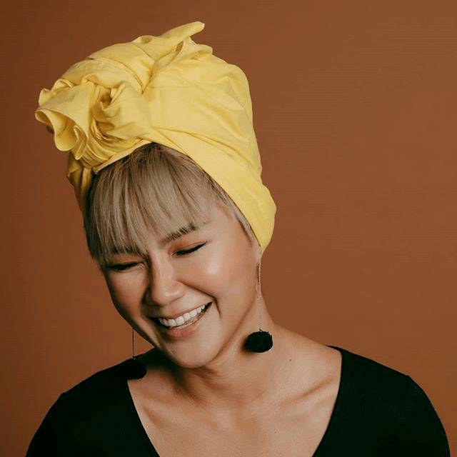Woman with blonde hair, yellow hair piece and black earrings