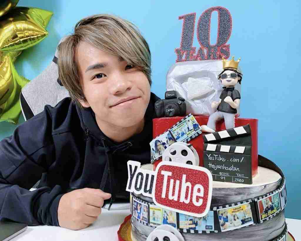 Guy with grey hair smiling behind 10 year youtube cake