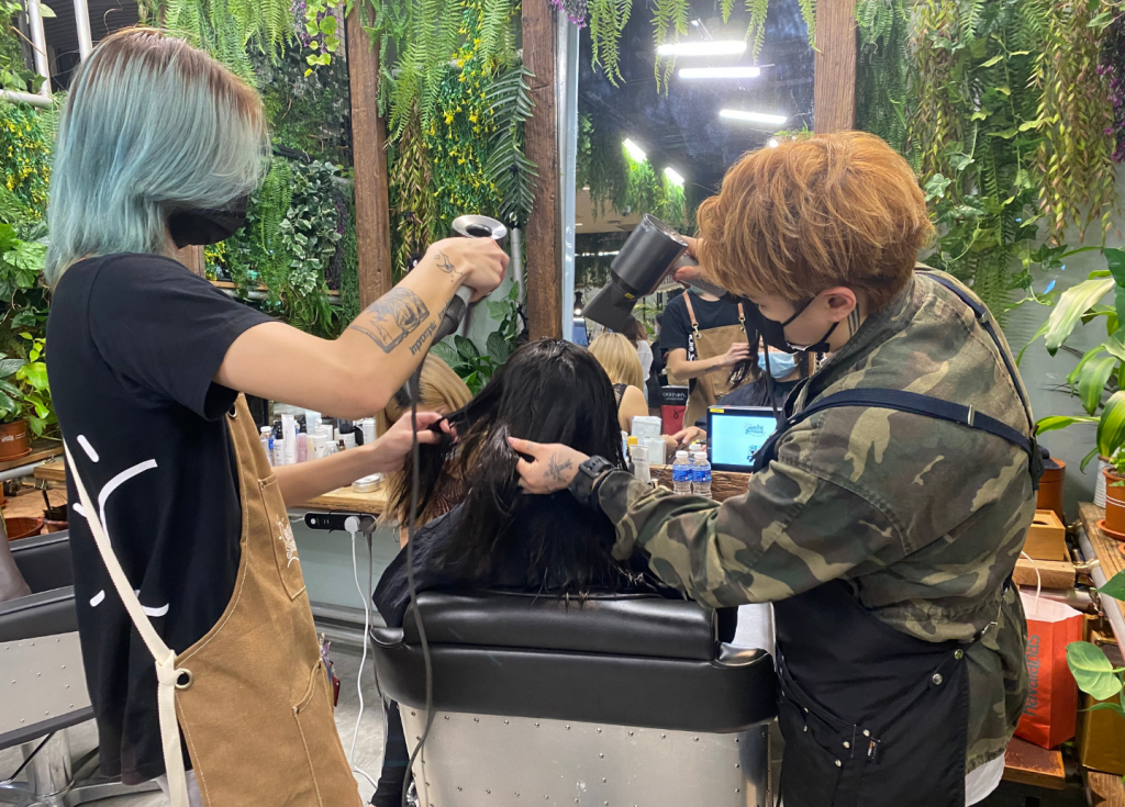 Hair stylists blowing dry the hair of a customer
