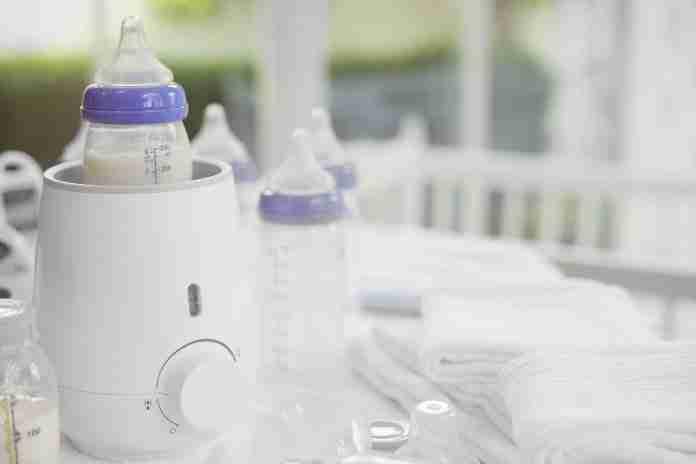 Baby bottle with milk warming in a bottle warmer